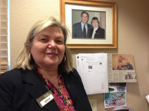"Verica Weikal posing next to the picture taken of her meeting President George W. Bush.  She said he was a ""hugger"", which he had learned from his mother Barbara."
